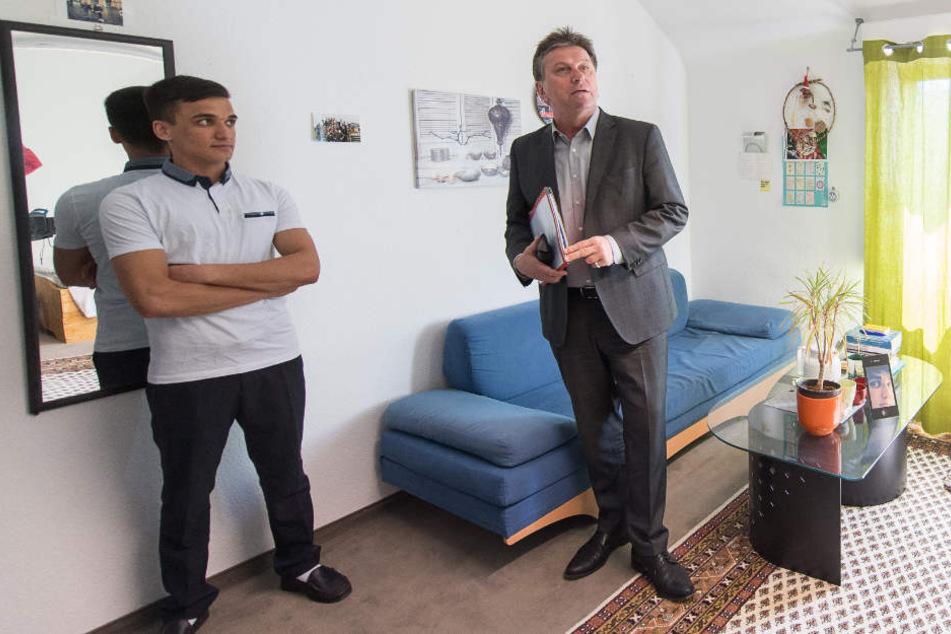 Manfred Lucha (Bündnis 90/Die Grünen), Sozialminister von Baden-Württemberg, (r.) schaut sich während einem Besuch in einem Haus mit Wohngruppen für unbegleitete minderjährige Flüchtlinge das Zimmer eines Flüchtlings an.