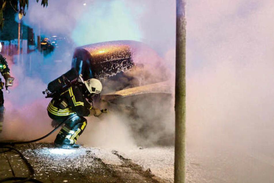 Kameraden der Feuerwehr löschen einen Dienstwagen der Deutschen Bahn in Leipzig-Leutzsch. Er fiel offenbar Brandstiftern zum Opfer.