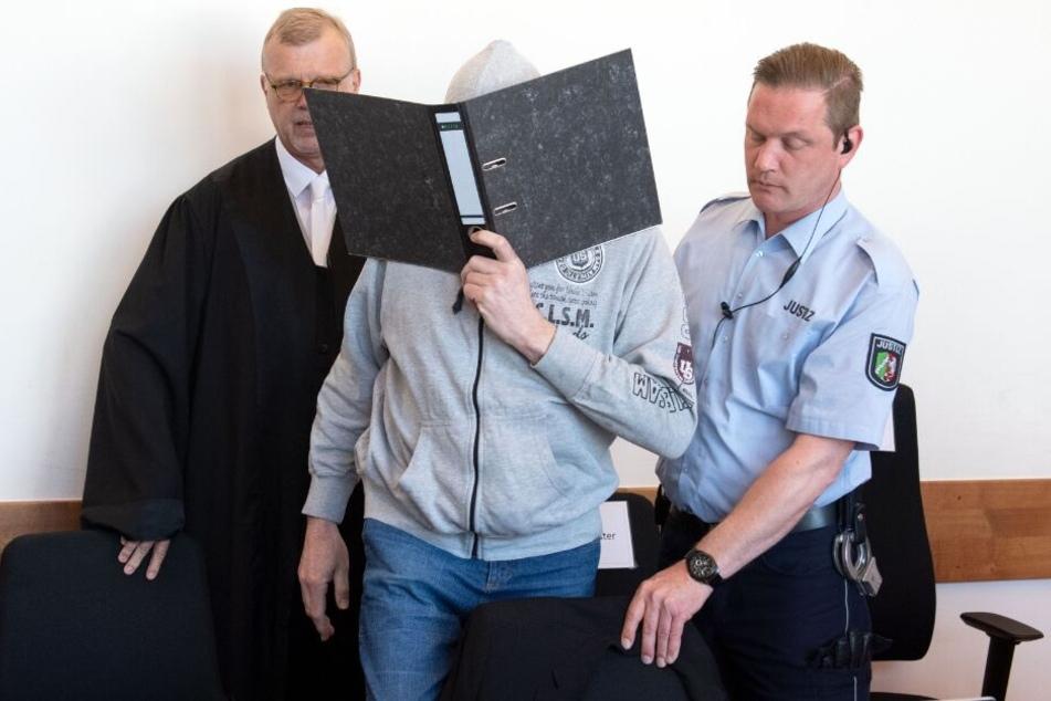 Der Hauptangeklagte Andreas V. versteckte sein Gesicht hinter einem Aktenordner, als er in den Gerichtssaal geführt wurde.