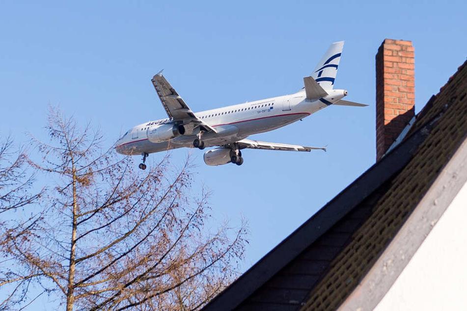 Ein Flugzeug fliegt gut sicht- und hörbar über ein Hausdach hinweg (Symbolfoto).