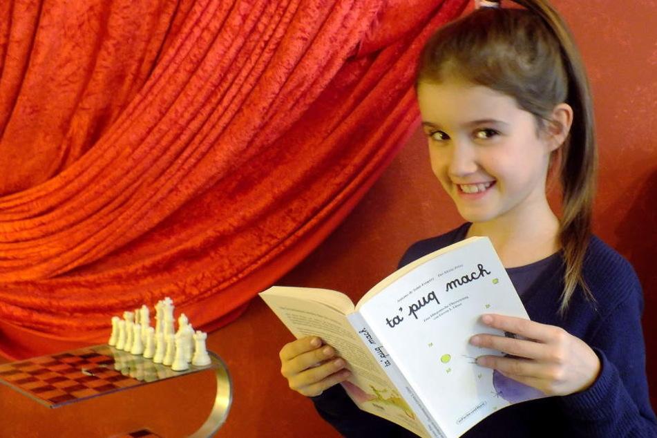"""Die siebenjährige Aurélie Litaer hält das Buch """"Der Kleine Prinz"""" auf Klingonisch in den Händen."""