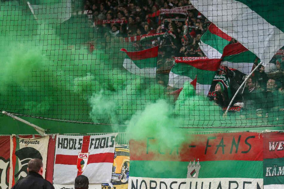 Fans aus Augsburg zünden bengalisches Feuer mit grünen Rauchwolken.
