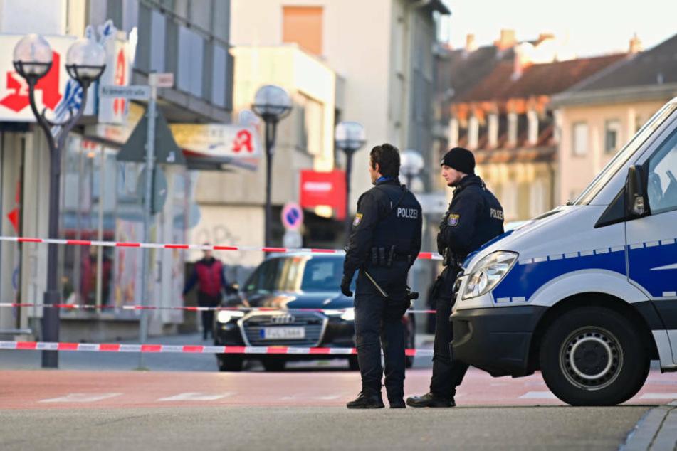 Polizisten stehen in der Nähe eines Tatortes am Heumarkt in Hanau.