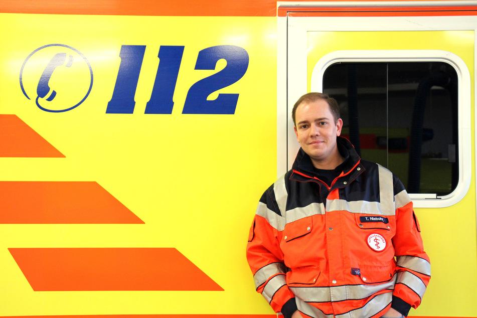 Der Notfallsanitäter Timo Niebuhr steht an einen Rettungswagen gelehnt.