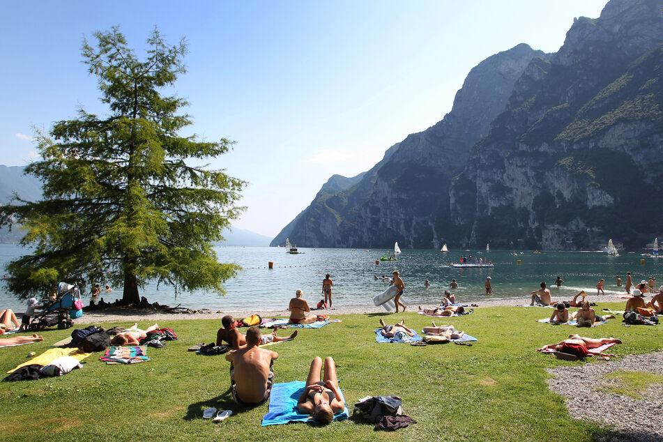 Touristen und Einheimische nehmen am Strand von Riva del Garda ein Sonnenbad. (Archivbild)