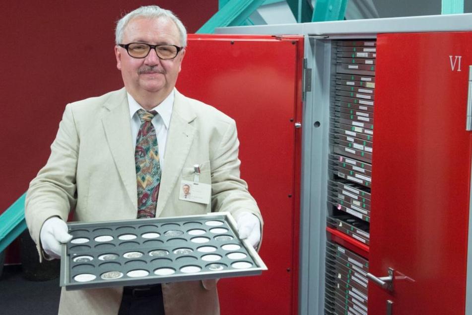 Rainer Grund, Direktor des Münzkabinetts, hält im Depot des Kabinetts in Dresden ein Tablett mit verschieden Münzen, die vorsorglich ins Depot verbracht wurden.