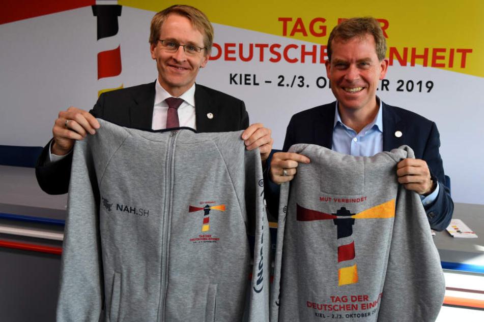 Freiwillige Helfer werden diese Jacken tragen, die Daniel Günther (CDU, links), Ministerpräsident von Schleswig-Holstein und Ulf Kämpfer (SPD), Kieler Oberbürgermeister, präsentieren.