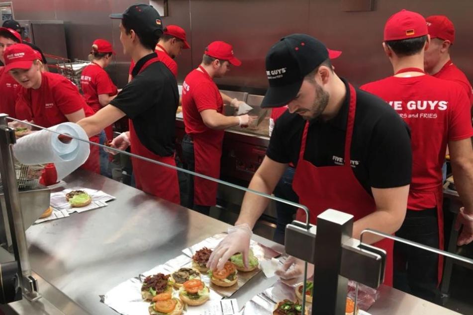 Die ersten Burger werden von den Mitarbeitern zubereitet.