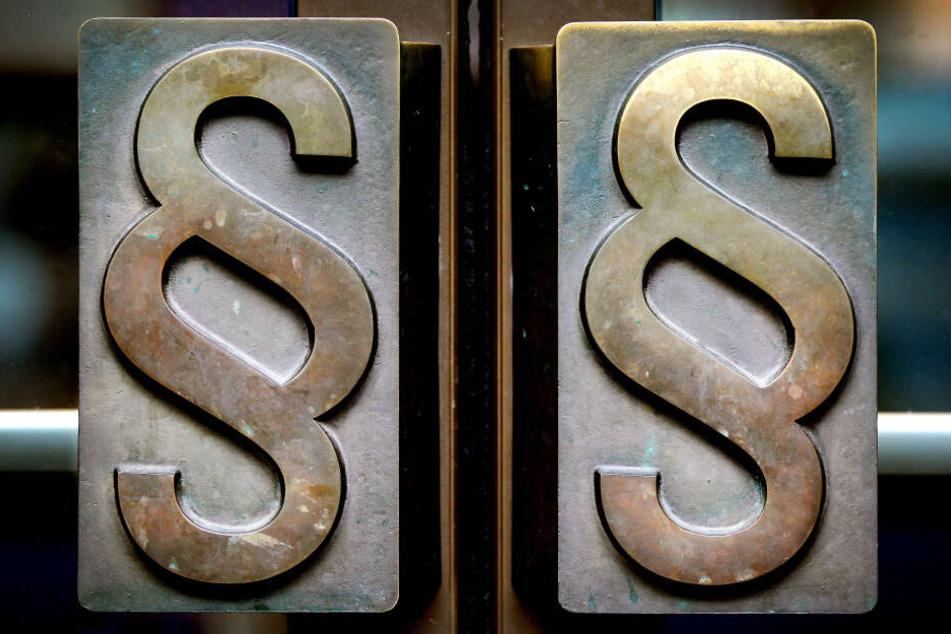 Paragrafen-Symbole prangen an Türgriffen am Eingang eines deutschen Landgerichts (Symbolbild).