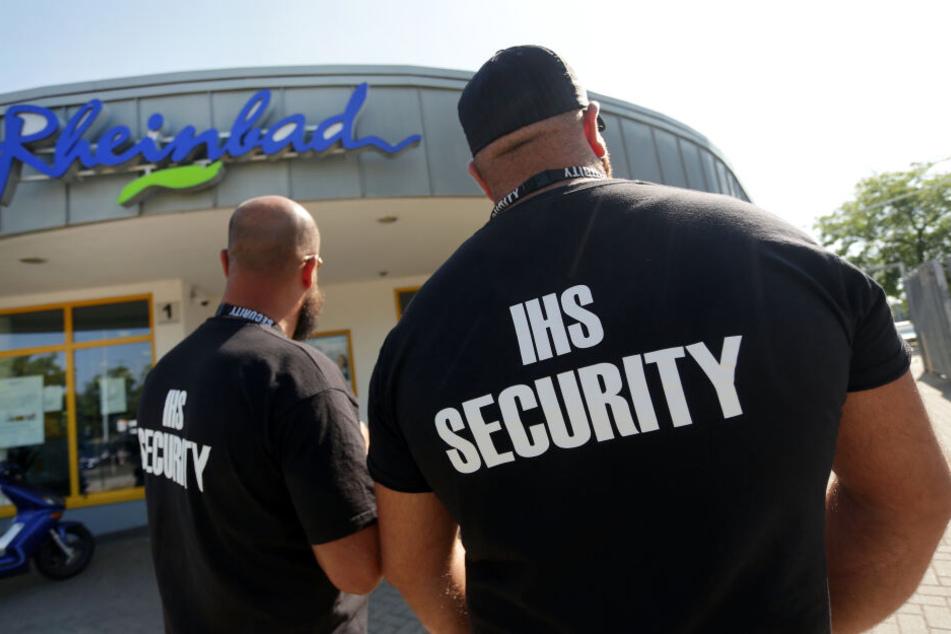 Zwei Männer des Sicherheitsdienstes IHS Security stehen vor dem Eingang des Rheinbades.