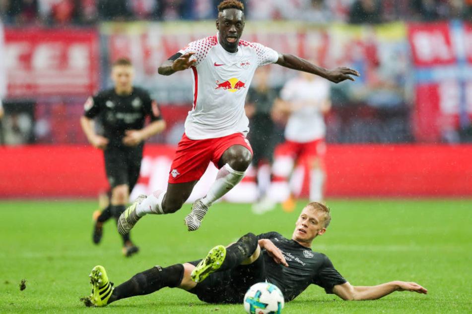 Leipzigs Jean-Kevin Augustin springt über Stuttgarts Timo Baumgartl.