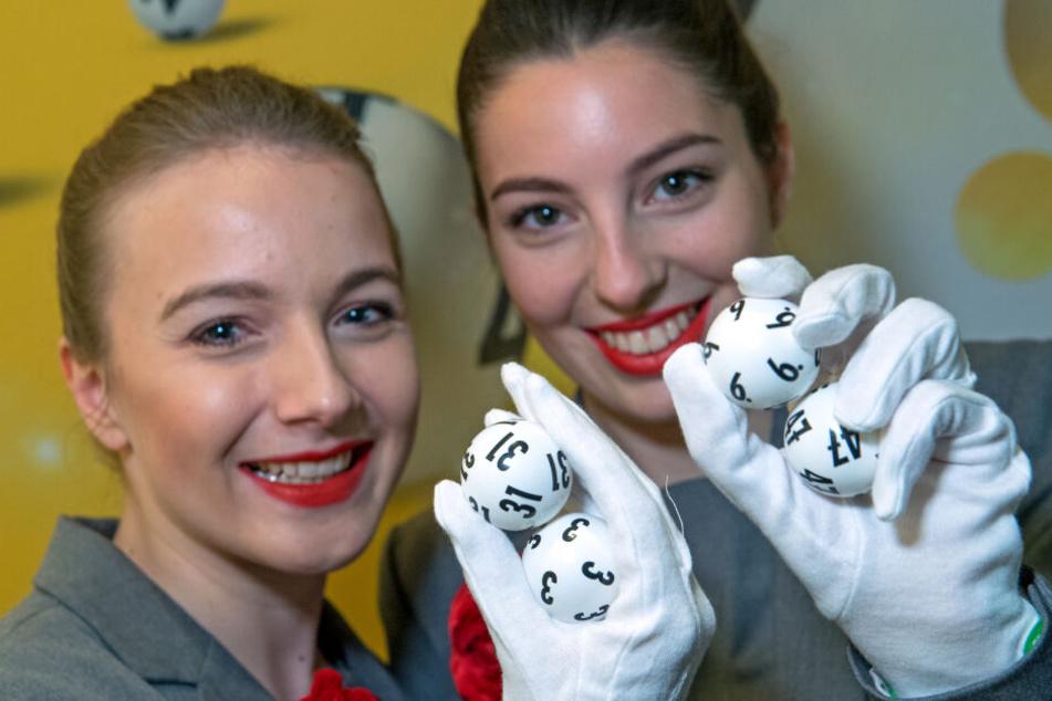 Die Sachsenlotto-Hostessen Lea Krebs (l.) und Franziska Henck halten die am häufigsten gezogenen Original-Lottozahlen in ihren Händen.
