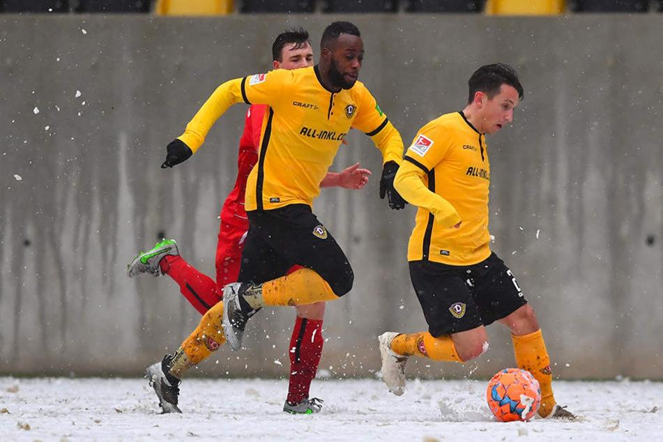Dynamos Baris Atik (r.) führt den Ball auf dem schneebedecktem Geläuf und wird von Erich Berko (M.) überlaufen.