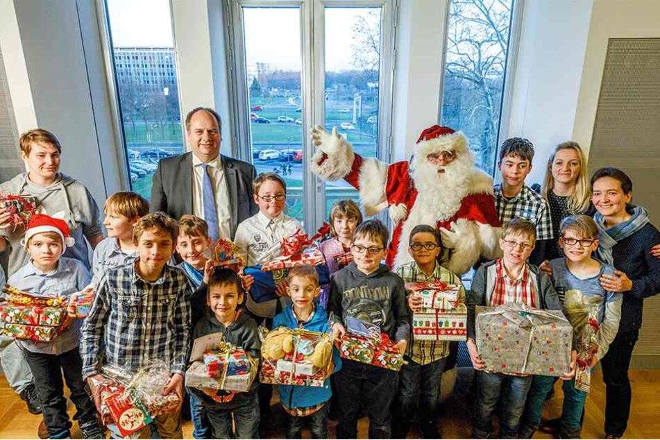 Kein Kind blieb ohne Geschenk - Weihnachtsmann und OB Dirk Hilbert (hinten) hatten alle Hände voll beim Verteilen der Gaben zu tun.