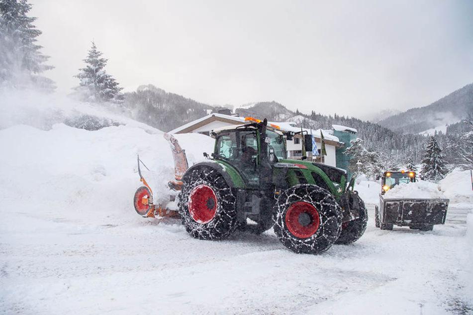 Eine Schneefräse und ein Radlader räumen einen zugeschneiten Parkplatz.