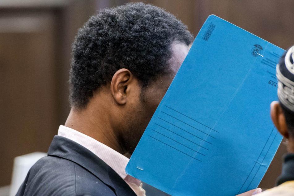 Der Verurteilte versteckt sein Gesicht vor Gericht hinter einer Mappe.