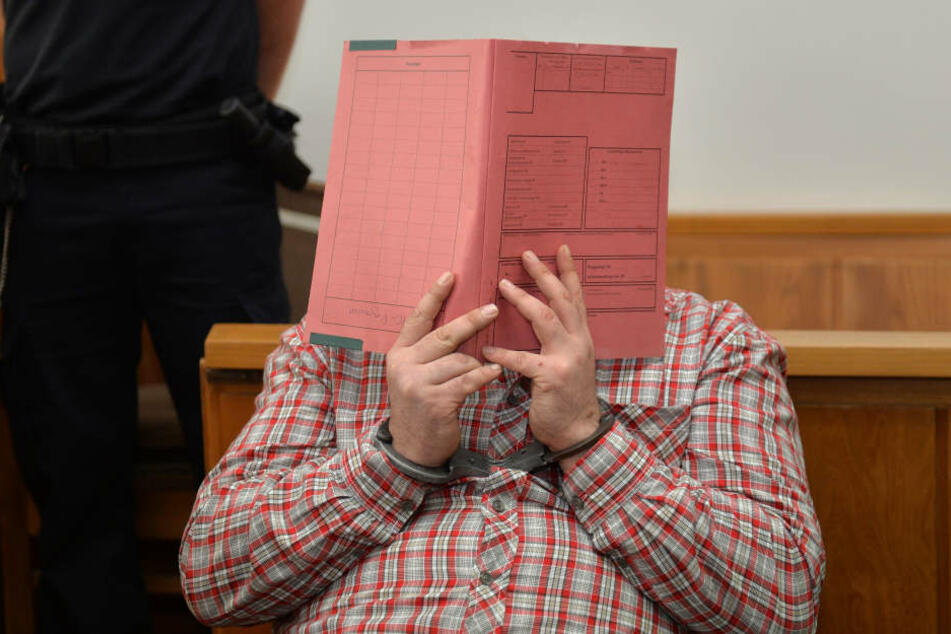 Der Angeklagte Niels H. verbirgt sein Gesicht hinter einer Aktenmappe.
