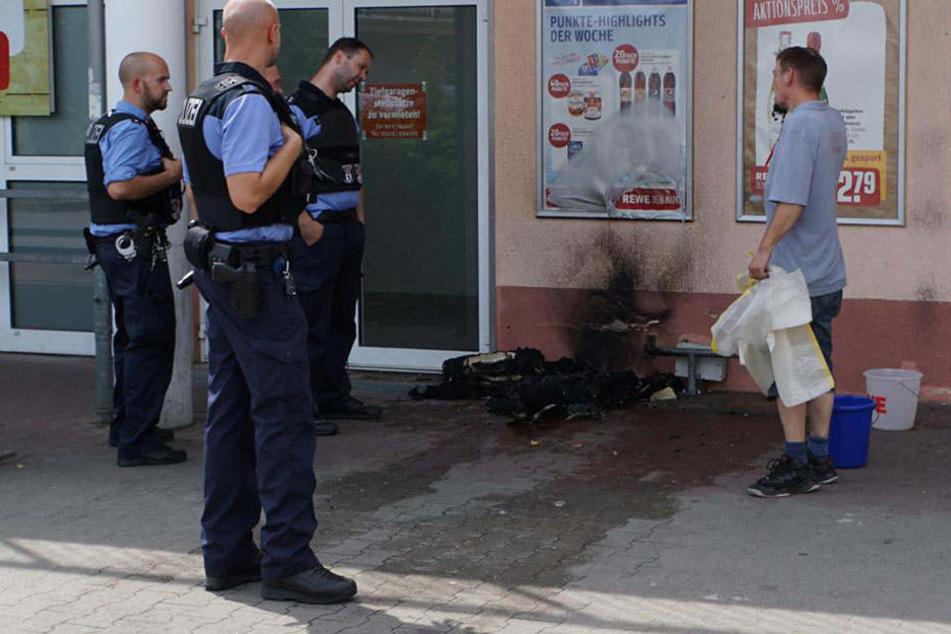 Die Beamten begutachten die Überreste des Brandes und befragen Zeugen.
