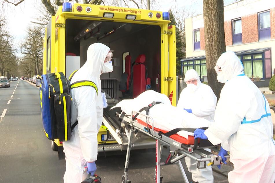 In Schutzanzügen verfrachten Rettungskräfte den Bewohner in einen Krankenwagen.