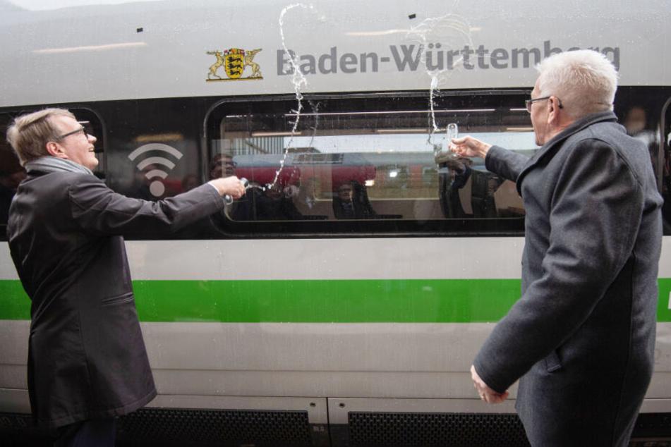 Winfried Kretschmann (rechts im Bild) und Ronald Pofalla schütten Sekt auf einen ICE 4.