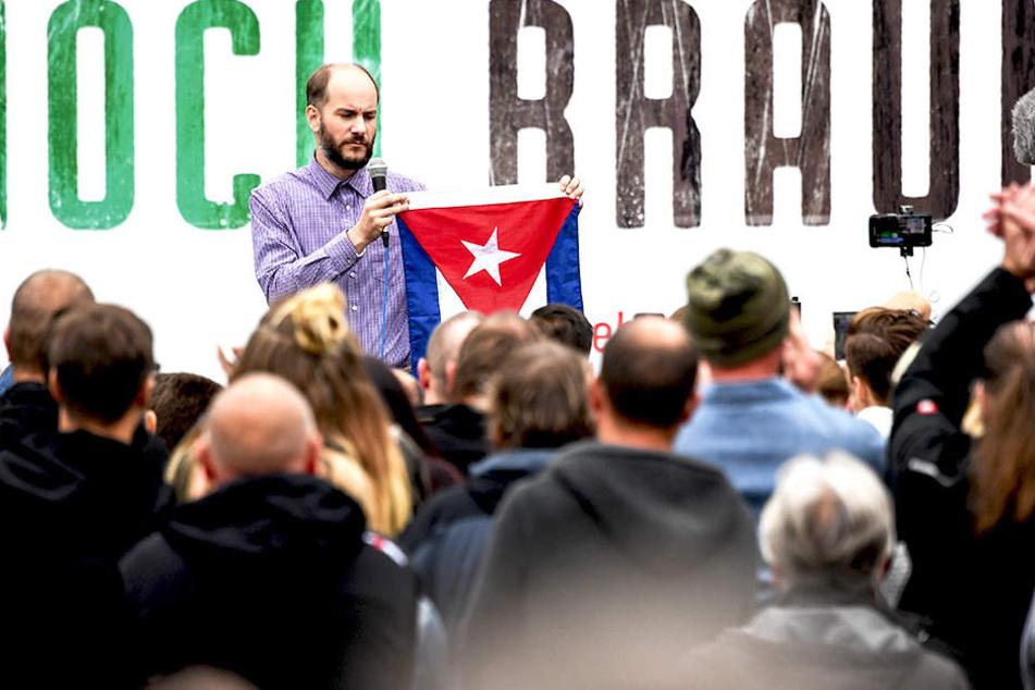 """Bei der Kundgebung von """"Pro Chemnitz"""" hält Martin Kohlmann eine Kuba-Flagge hoch."""