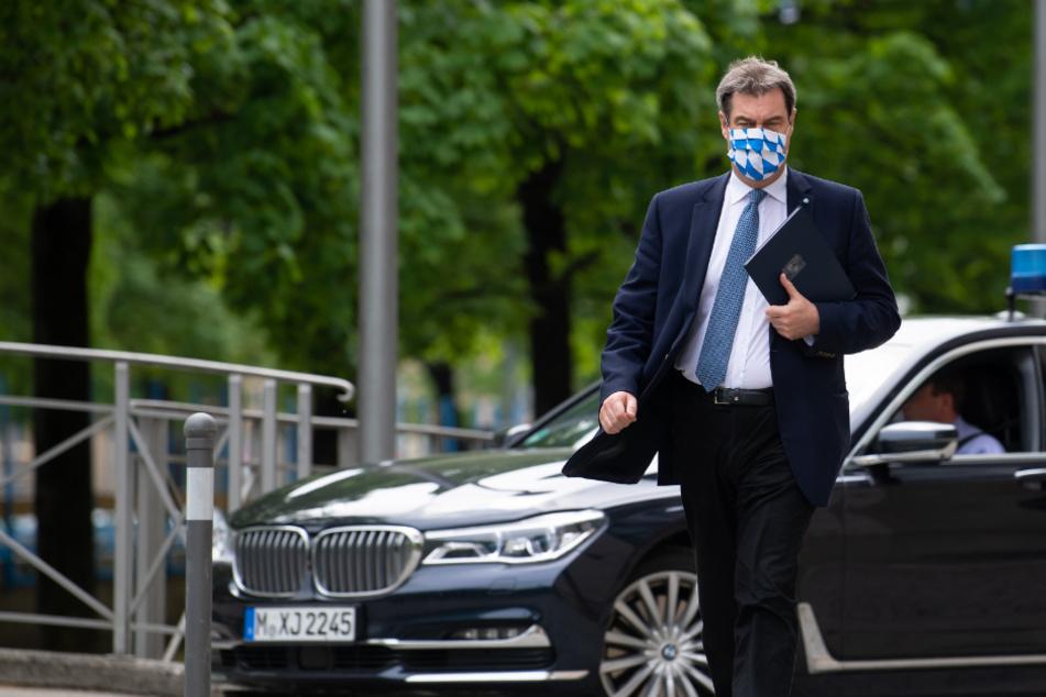 Markus Söder (CSU), Ministerpräsident von Bayern, kommt nach einer Sitzung des bayerischen Kabinetts mit Mundschutz zu einer Pressekonferenz.