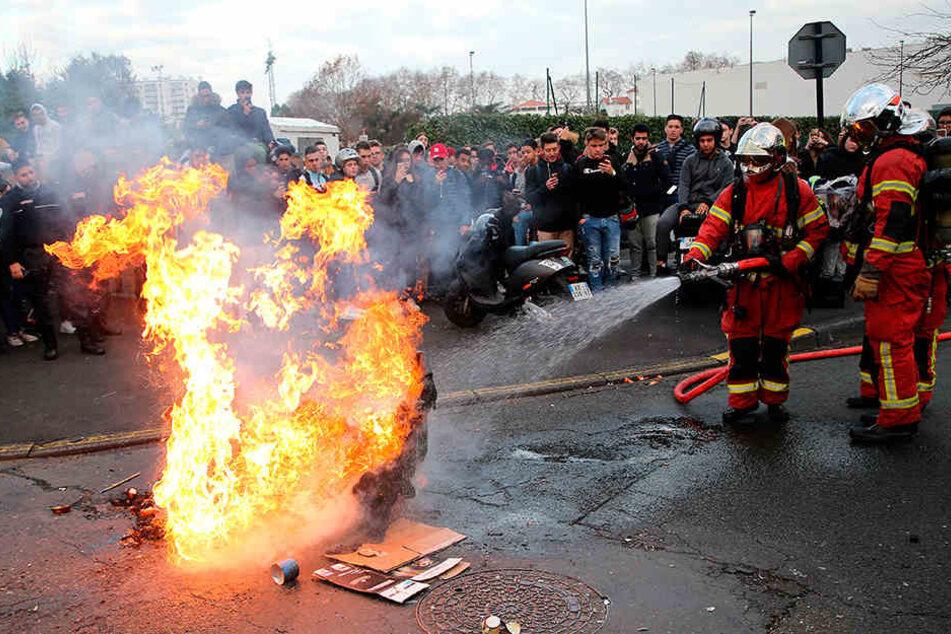 Feuerwehrmänner löschen eine brennende Mülltonne auf einem Schulhof im französischen Bayonne.