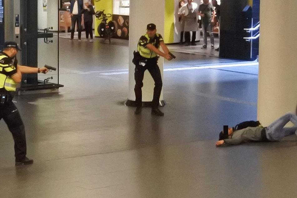 Polizisten richten ihre Waffen auf den verwundeten Täter (19).