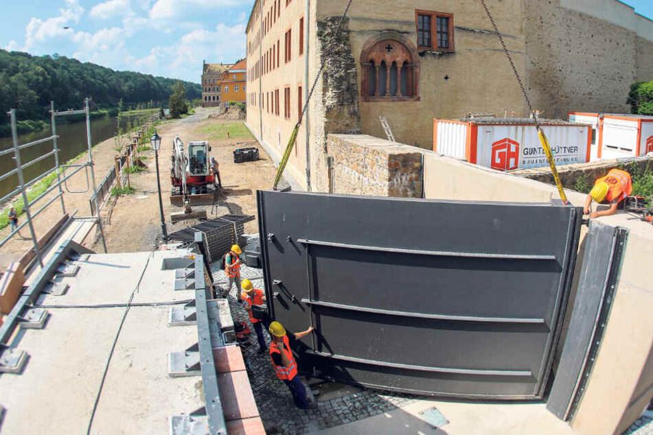 Mit einem Kran wird das letzte Tor für die Hochwasserschutzanlage eingehoben und damit die letzte Lücke in der Flutmauer geschlossen.