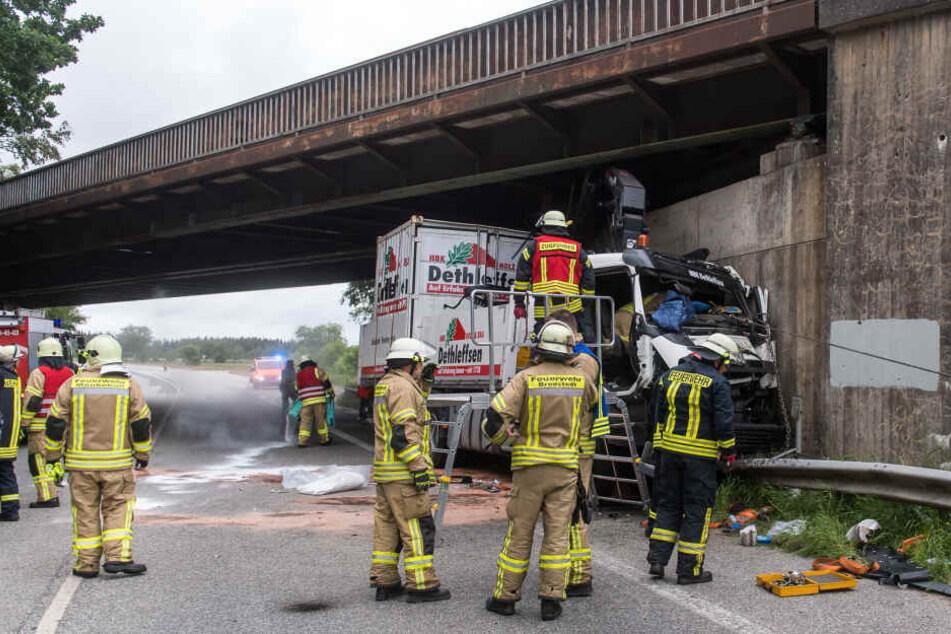 Feuerwehrmänner arbeiten an einem Lastwagen, der eine Eisenbahnbrücke gerammt hat