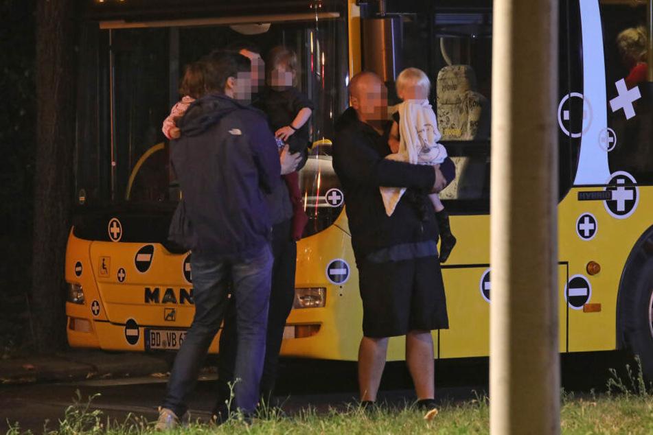Bewohner mit ihren Kindern am Bus der DVB, der bereitgestellt wurde, um die Menschen zu versorgen.