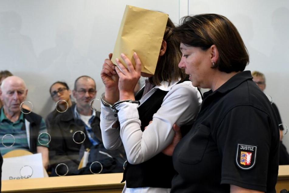 Mit verdecktem Gesicht wird die Angeklagte zum Auftakt eines Mordprozesses in den Gerichtssaal geführt.