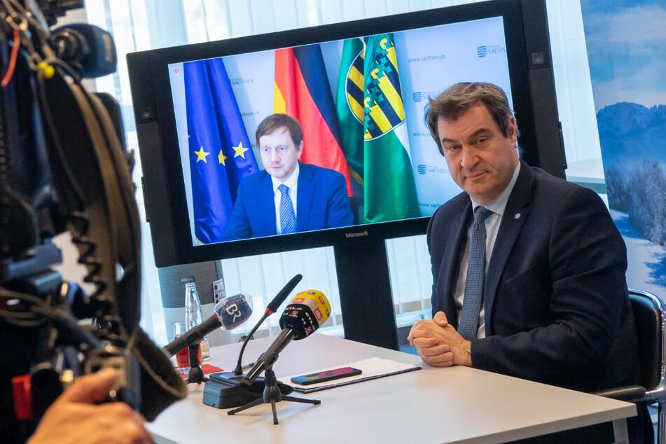 Markus Söder (r, CSU), Ministerpräsident von Bayern, nimmt in der Staatskanzlei an einer Online-Pk von Bayern und Sachsen zur Covid-19-Allianz der beiden Bundesländer teil. Auf dem Bildschirm ist Michael Kretschmer, (CDU) Ministerpräsident von Sachsen zu sehen.