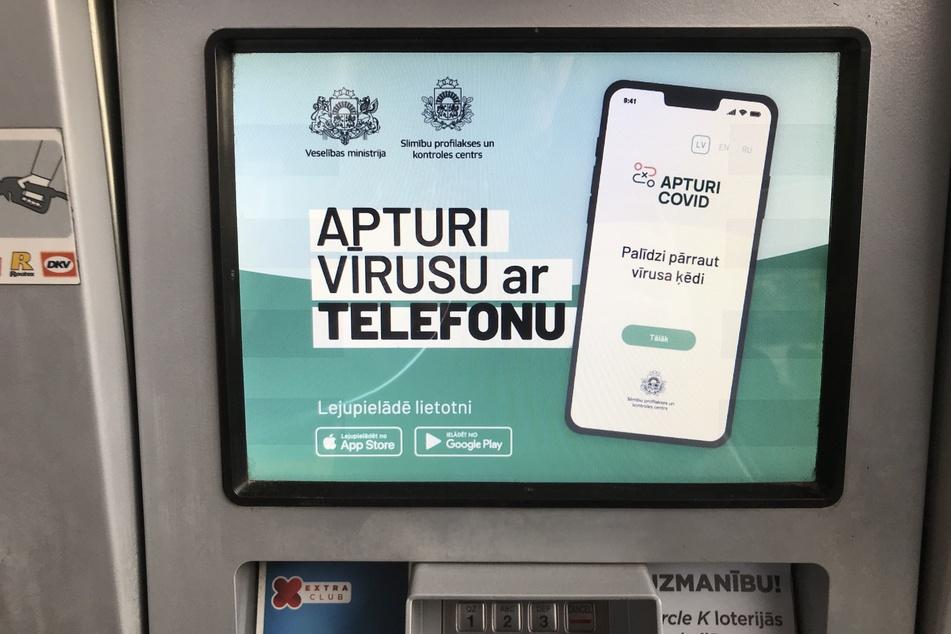 """Eine Anzeige auf einem Multimedia-Display einer Zapfsäule an einer Tankstelle der lettischen Hauptstadt. Mit dem Slogan """"Apturi Virusu ar Telefonu"""" (Stop den Virus mit dem Telefon) wird darauf die lettische Corona-Warn-App beworben."""
