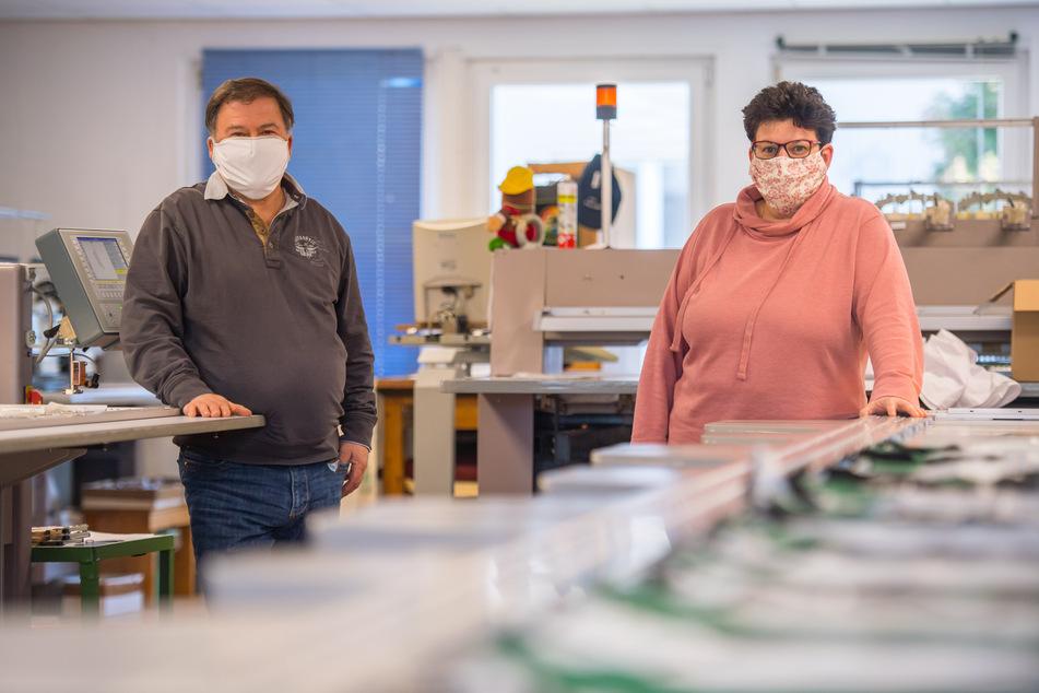 Geschäftsführer Hartmut Funke und die stellvertretende Geschäftsführerin Anke Scheibner tragen die Prototypen der Schutzmasken.
