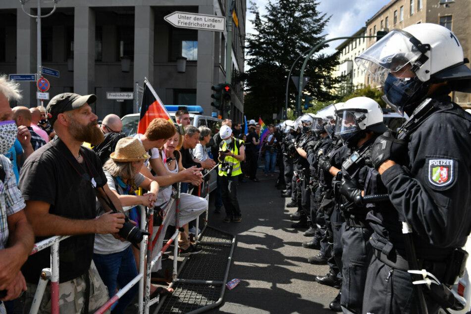 Eine Polizeikette steht an Absperrgittern den Teilnehmern gegenüber bei einer Demonstration gegen die Corona-Maßnahmen. F