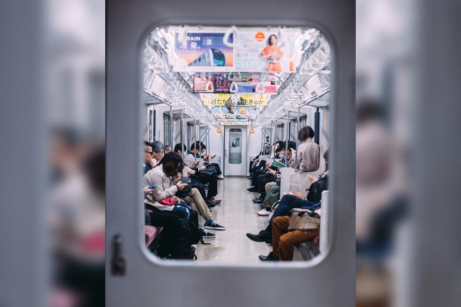 Blick in eine U-Bahn in Tokio. Viele Japaner schauen auf ihre Handys.