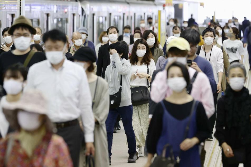 Pendler mit Gesichtsmasken laufen am Bahnhof Fukuoka im Südwesten Japans über einen Bahnsteig.