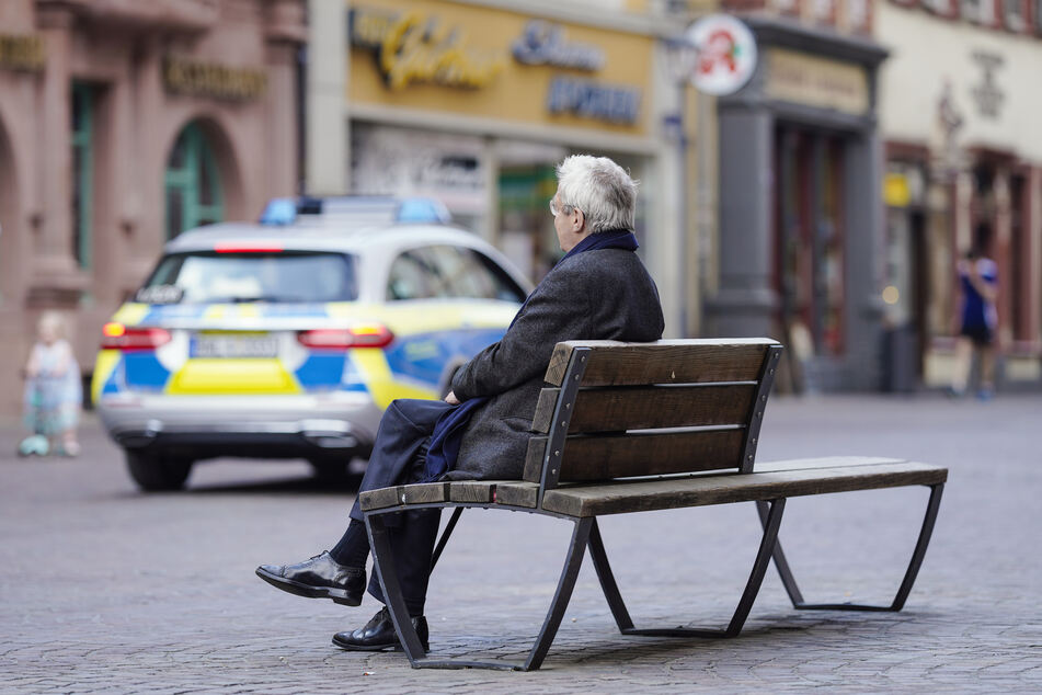 Ein Mann sitzt in der Fußgängerzone alleine auf einer Bank, während im Hintergrund ein Polizeiauto vorbei fährt.