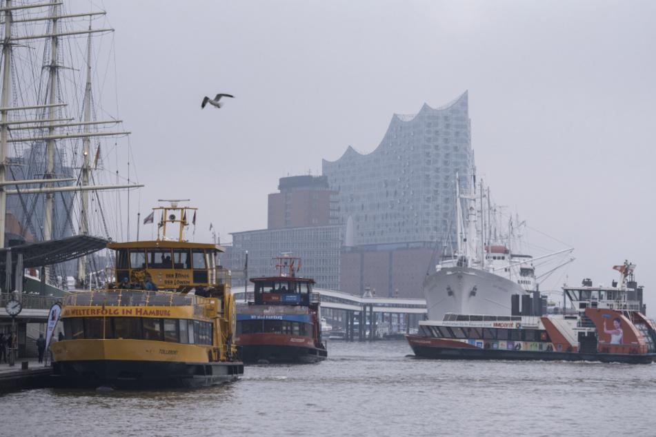 Fähren fahren bei trübem Wetter im Hafen auf der Elbe. Im Hintergrund ist die Elbphilharmonie zu sehen.