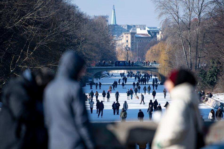 Die Menschen nutzen das sonnige Wetter, um über den zugefrorenen Landwehrkanal zu laufen.