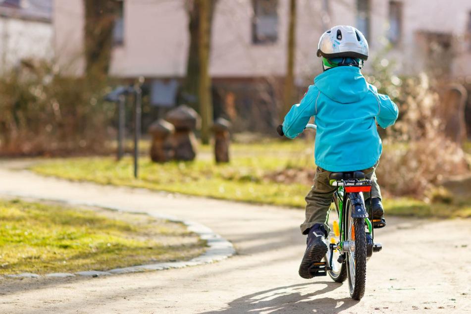 Ein kleiner Junge fährt mit seinem Fahrrad im Stadtpark. (Symbolbild)