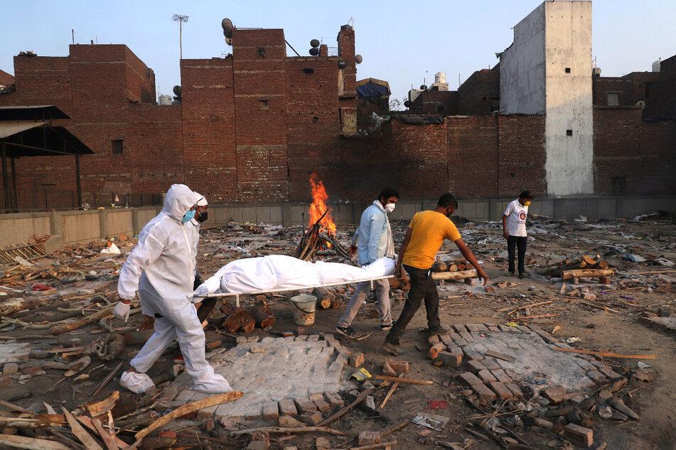 Neu Delhi: Familienmitglieder und Freiwillige tragen den Leichnam eines Corona-Opfers zur Einäscherung.