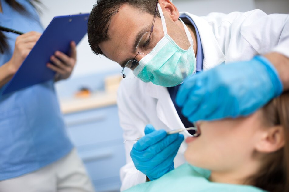 A dentist checks his patient's teeth (stock image).