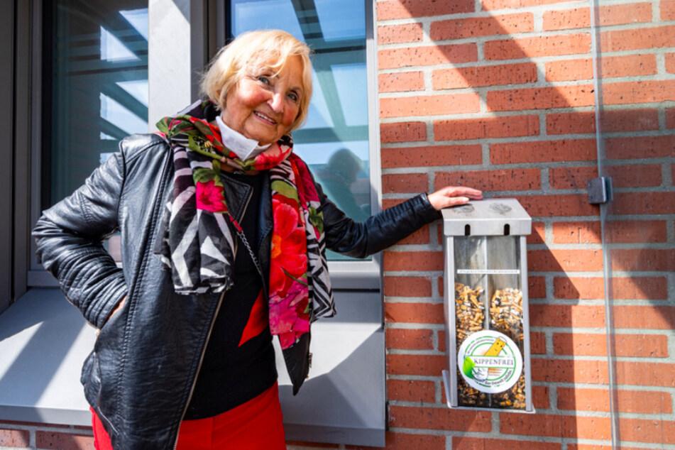 """Karin Meixner-Nentwig (82), von dem Verein """"Amberger Kippenjäger"""" steht neben einem Sammelbehälter mit Zigarettenkippen."""
