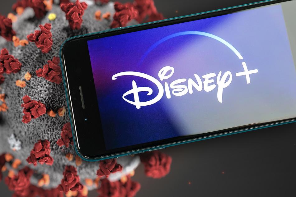 Ein Handy mit Disney+ vor der Ansicht eines Coronavirus. (Symbolbild)
