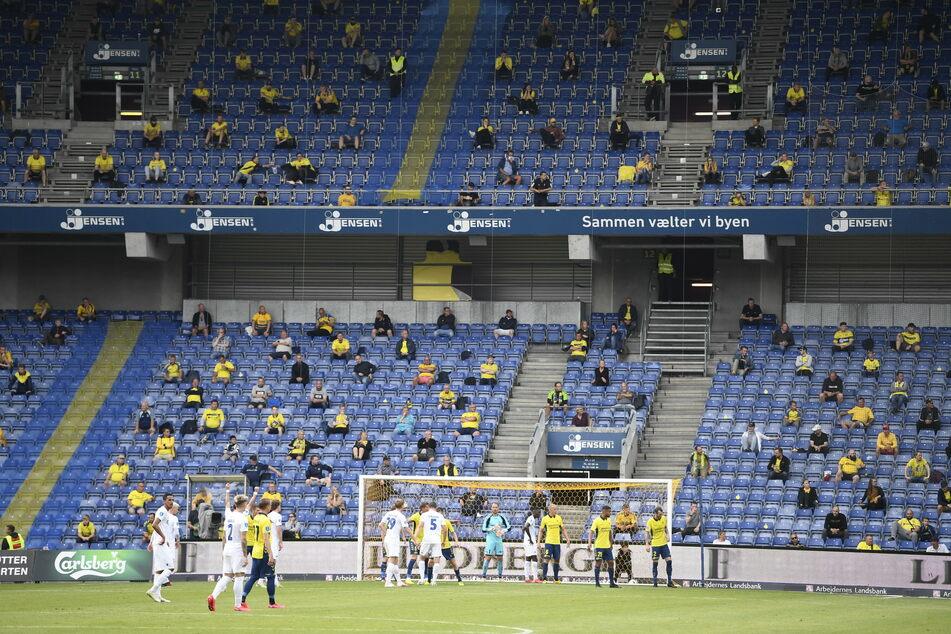 Fans verfolgen mit Mindestabstand voneinander auf der Zuschauertribüne das Spiel des Bröndby IF gegen den FC Kopenhagen.