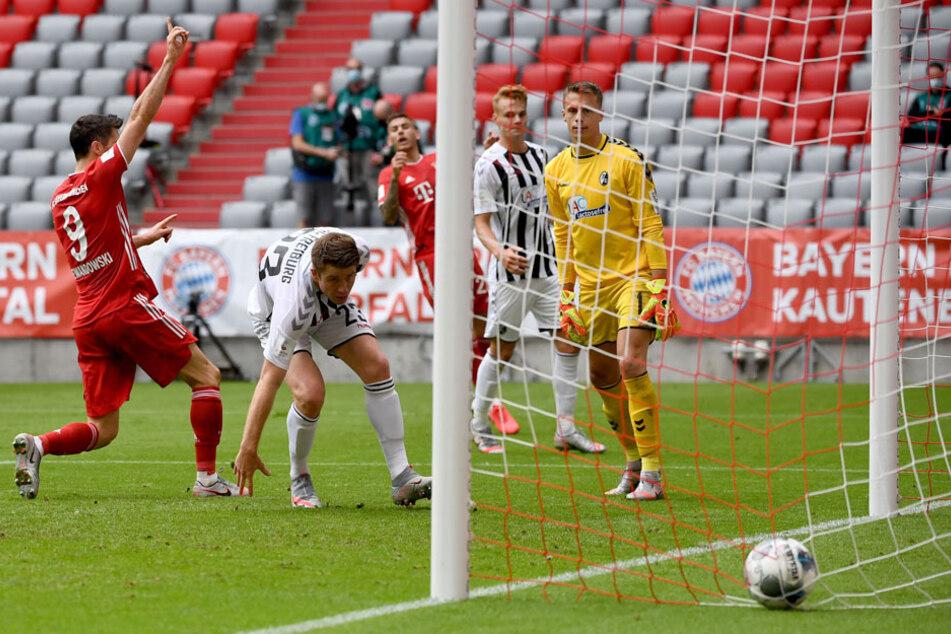Robert Lewandowski (l.) erzielt den Treffer zum 3:1 gegen Freiburgs Torwart Alexander Schwolow (r.).
