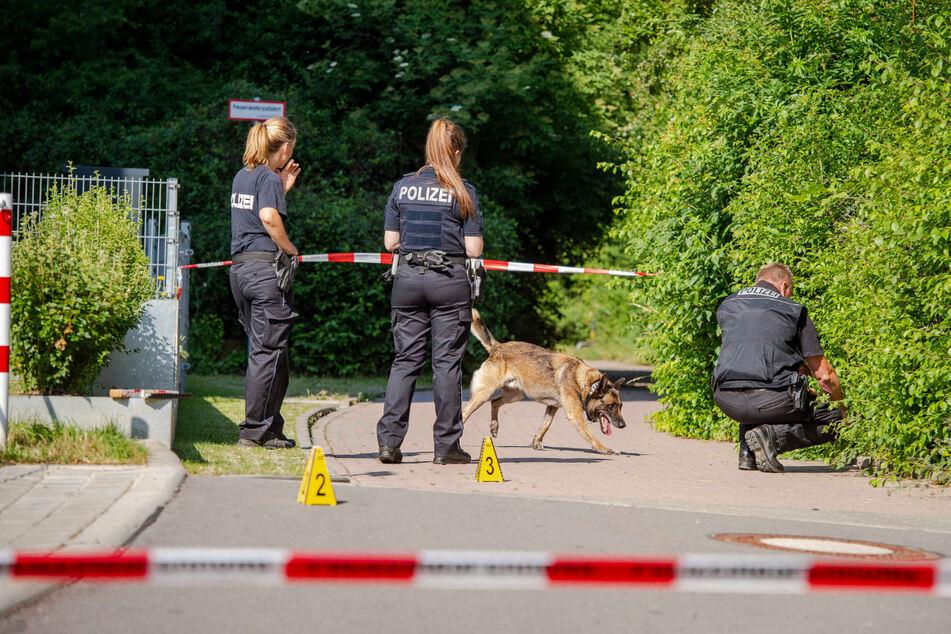 Zwei Polizistinnen, ein Polizist und ein Hund sind am Ort der Messerattacke in Erfurt. Der Bereich ist abgesperrt.