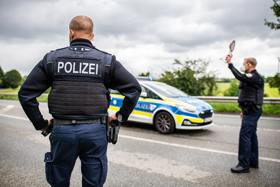 Ein Polizeibeamter steht bei einer Corona-Einreisekontrolle der Bundespolizei an der deutsch-niederländischen Grenze mit einem Polizeianhaltestab und kontrolliert Fahrzeuge im Grenzgebiet.